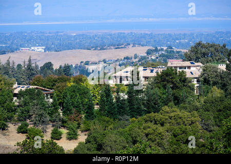Mansions on the hills surrounding San Francisco bay area; the bay shoreline visible in the background - Stock Photo