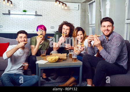 A group of friends eating pizza wathing tv sitting on the couch. - Stock Photo