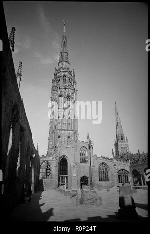 Spire of the ruined St Michael's Cathedral Church, Coventry, West Midlands, c1955-c1980. view from inside the ruins, possibly from the southern aisle, looking west with the top of the Holy Trinity Church spire in the background. The external walls are standing, with the crennellated pinnacles separating each bay of the aisle standing. Inside the church are low portions of the internal columns. The church was one of the largest medieval parish churches and was made a cathedral in 1918. The damage was caused by a German air rain in November 1940. Originally built in the 12th century, Holy Trinit - Stock Photo