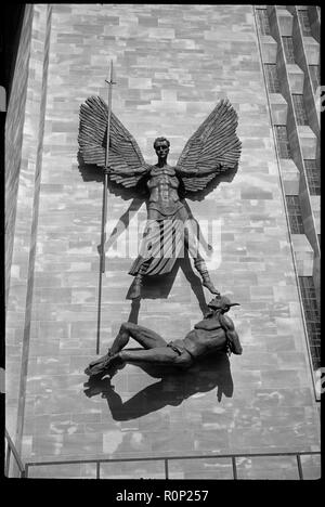 'St Michael's Victory over the Devil', sculpture at Coventry Cathedral, West Midlands, c1958-c1980. Detail of the sculpture depicting St Michael over Lucifer holding a long spear in his right hand, arms and wings outstretched, with Lucifer's feet bound by chains and his arms bound behind his back, attached on the exterior of the baptistery wall of the new Coventry Cathderal.The sculpture is by Jacob Epstein and is attached to the baptistery wall near the porch. It is hung so that Lucifer's nearly horizontal body aligns with the top of the steps that ascend towards the porch, and the top of St  - Stock Photo