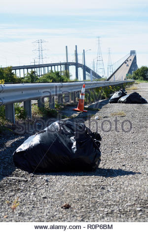 Don't Mess With Texas. Trash on Road at Rainbow Bridge in Bridge City Texas. Garbage Bag, refuse, junk, cone, guardrail, bridge. Illegal Dumping Texas - Stock Photo