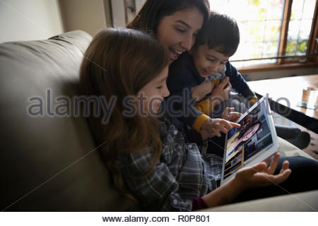 Latinx family video chatting with digital tablet on sofa - Stock Photo