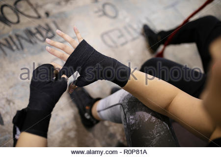 Female boxer wrapping wrist in gym - Stock Photo