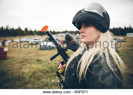 Confident young woman paintballing in field - Stock Photo
