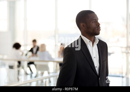 Thoughtful black employee look in distance dreaming of success - Stock Photo