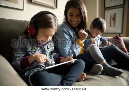 Latinx mother watching kids using digital tablets on sofa - Stock Photo
