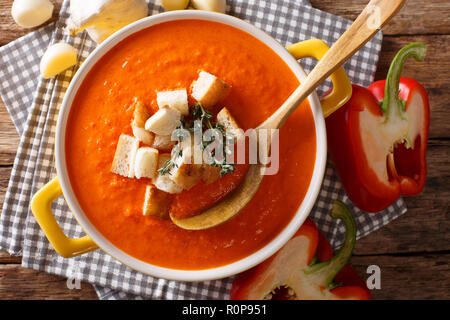 Dietary cream soup with sweet pepper and croutons close-up on the table. horizontal top view from above - Stock Photo