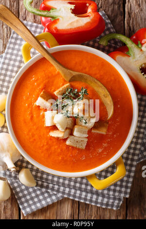 Dietary cream soup with sweet pepper and croutons close-up on the table. Vertical top view from above - Stock Photo