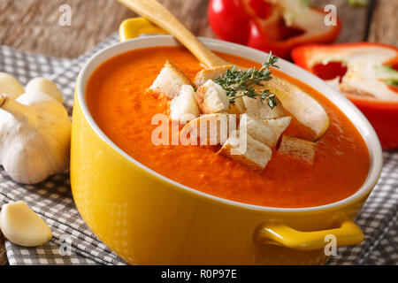 Summer thick cream soup of sweet pepper with croutons and herbs close-up on the table. horizontal - Stock Photo
