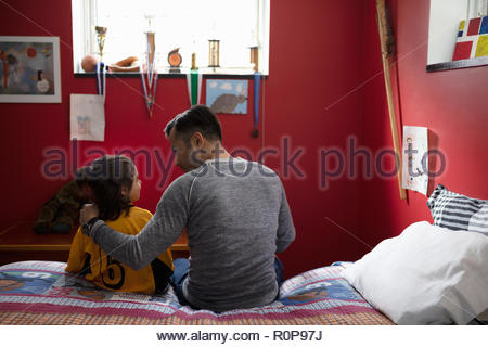Father talking to son in soccer uniform on bed - Stock Photo