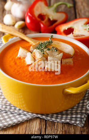 Dietary cream soup with sweet pepper and croutons close-up on the table. vertical - Stock Photo