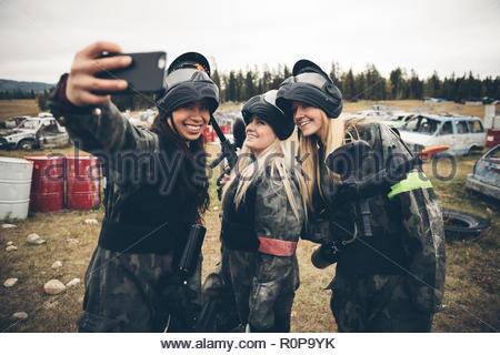 Women friends paintballing, taking selfie in field - Stock Photo