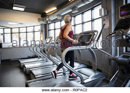 Senior woman walking on treadmill in gym - Stock Photo