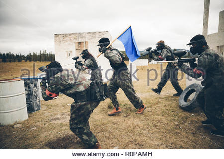 Paintballing team with blue flag in field - Stock Photo