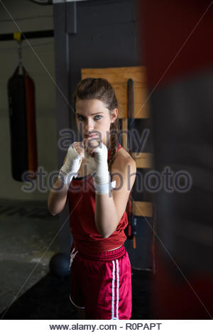 Tough female boxer training at punching bag in gym - Stock Photo