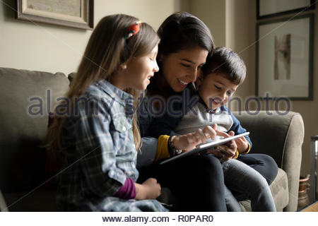 Latinx mother and children using digital tablet on sofa - Stock Photo