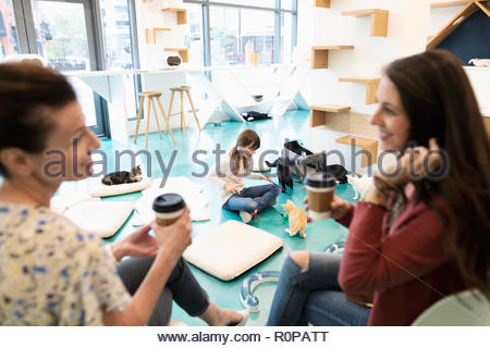 Women friends drinking coffee and talking while girl plays with kittens in cat cafe - Stock Photo