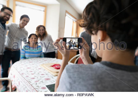 Latinx boy with camera phone photographing family - Stock Photo