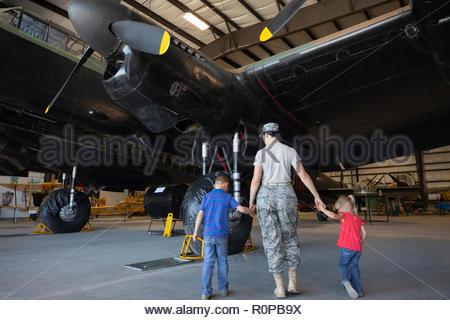 Female army engineer mother walking with children in military airplane hangar - Stock Photo