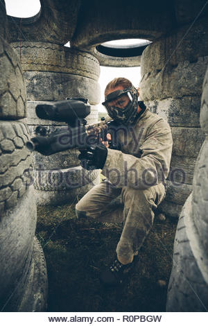 Portrait man hiding among tires, paintballing - Stock Photo