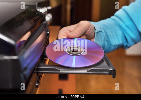 Hand holding DVD inserting to video player - Stock Photo