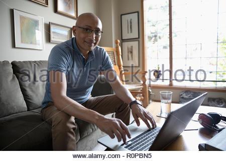 Portrait confident Latinx man using laptop in living room - Stock Photo