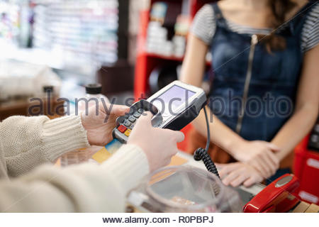 Close up female shopper paying, using credit card reader pin entry - Stock Photo