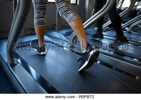 Legs of woman walking on treadmill in gym - Stock Photo