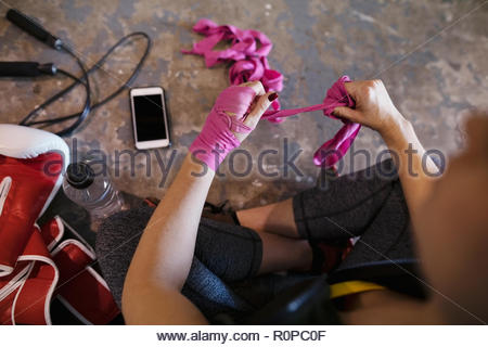 Female boxer wrapping wrists with pink tape - Stock Photo