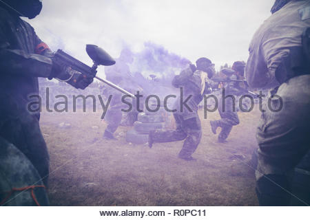 Friends paintballing, running in field with blue smoke - Stock Photo