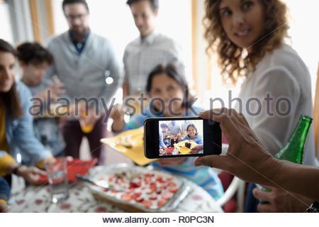 Man with camera phone photographing multi-generation family celebrating birthday with cake - Stock Photo