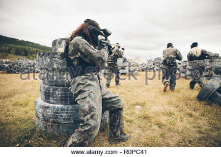 Friends paintballing in field with tires - Stock Photo