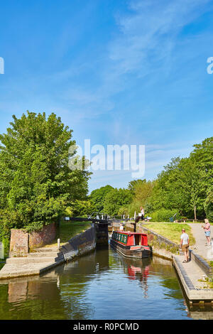 A red painted barge on the Kennet and Avon canal with people looking on just after passing through a lock on a sunny day, Newbury, Berkshire, UK - Stock Photo