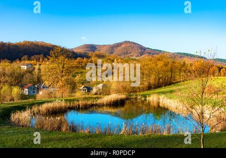 Beautiful autumn landscape with traditional houses and a lake in Sighetu Marmatiei, Maramures region - Romania - Stock Photo
