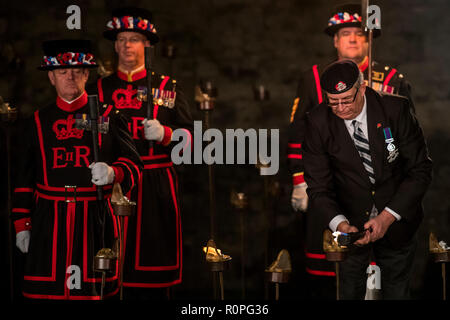 London, UK, 06th November 2018 A veteran begins to light the lanterns - Tower of London Beyond The Deepening Shadow ceremony, where the moat is gradually filled with thousands of individual flames: a public act of remembrance for the lives of the fallen. It begins with a procession led by the Yeoman Warders of the Tower of London who ceremonially light the first flame. A select team of volunteers then proceed to light the rest of the installation, gradually creating a circle of light, radiating from the Tower. Credit: Guy Bell/Alamy Live News - Stock Photo