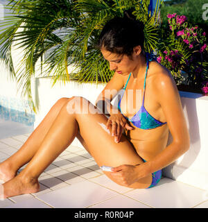 Young woman with blue bikini applying sun cream on her leg, poolside, Guadeloupe, French West Indies, - Stock Photo