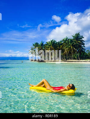 Young woman in red swimsuit sunbathing on yellow air mattress, floating on Caribbean sea, tropical beach, palm trees, Guadeloupe, French West Indies, - Stock Photo