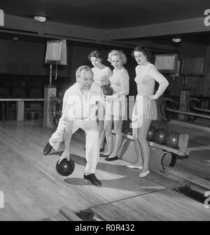 Bowling in the 1940s. A man is throwing the bowling ball and three young women are standing beside and looking. they are dressed in short striped skirts and jumpers. 1940s Sweden Photo Kristoffersson ref AY36-3