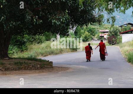 Two young Buddhist monks walking in Punakha, Bhutan - Stock Photo