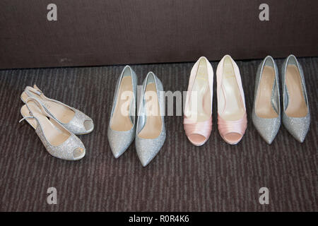 bride and bridesmaids shoes all lined up and ready to be worn on the wedding day - Stock Photo