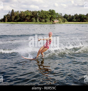 Waterskiing in the 1960s. A young woman in a patterned bathing suit passes the photographer on her waterskis. She has a typical bathing cap on. Sweden 1946 Photo Kristoffersson ref CV12-7 - Stock Photo