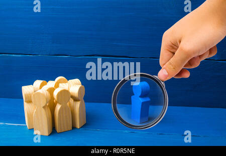 Magnifying glass is looking at the crowd of wooden figures of people stand distantly and look at the blue man. The person tries to establish contact w - Stock Photo