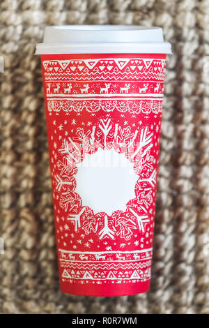 Paper coffee cup with red christmas pattern and empty place for title