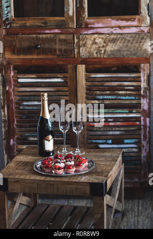 Delicious cupcakes and champagne for two on the vintage wooden table - Stock Photo