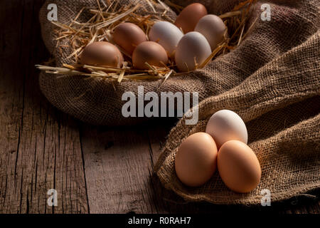 Fresh chicken eggs in farm lying on linen cloth on wooden table