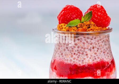 Closeup shot of glass jar filled with sweet raspberry jam and chia pudding and garnished with granola and fresh berries - Stock Photo
