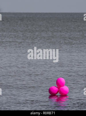 Pink balloons in the middle of the big ocean, representing a unique value, a total individual being - Stock Photo