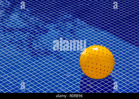 Yellow ball in the middle of a big textured pool, representing a unique value, a total individual being - Stock Photo