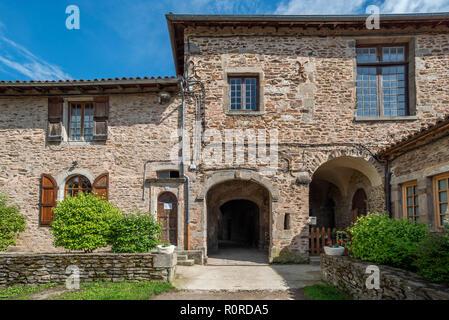 Monastic buildings with arched doorways and random stone walls define an external courtyard in the beautiful village of Sainte-Croix-en-Jarez - Stock Photo