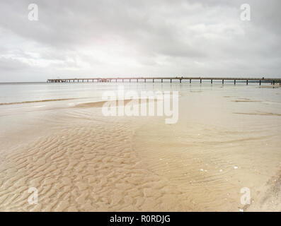 Sea Bridge above the Baltic Sea. Sun hidden at misty horizon, refletion in water. - Stock Photo